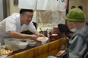 入居者に醤油ラーメンを手渡す木村さん(左)
