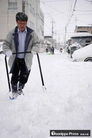 厳しい冷え込みの中、朝から雪かきに追われる市民=25日午前8時40分ごろ、青森市長島3丁目