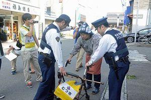 タグの位置情報を基に、行方不明になった高齢者役のスタッフ(中)を発見した警察官