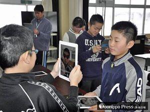タブレット端末で写真を撮り合う菖蒲川小の児童たち