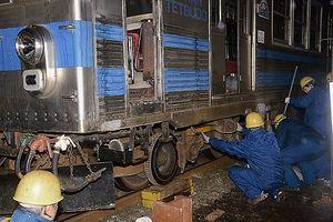 道具を使い、脱線した車体を持ち上げ線路に戻す作業員=15日午後7時ごろ、弘前市紙漉町