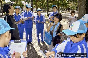 官庁街通りでまちなかガイドの事前研修を受ける十和田西高校生(水色の帽子)ら