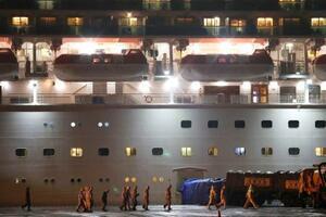 クルーズ船「ダイヤモンド・プリンセス」が停泊する横浜・大黒ふ頭を歩く防護服姿の人たち=16日午後8時47分