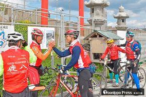 約800キロを自転車で走破し、ゴールの蕪島で健闘をたたえ合う参加者ら=5日午後2時
