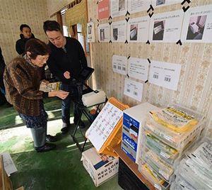 無人販売のシステムを使った買い物方法を、教わりながら体験する地域住民(手前左)