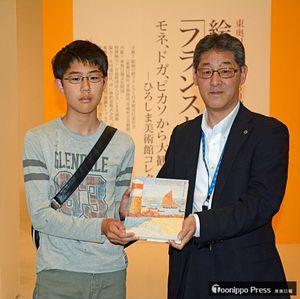 県立美術館の戸沼副館長(右)から記念品の図録を受け取る佐井さん