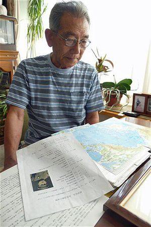 自宅で、自らまとめた父・岩蔵さんの資料を見る逢坂さん
