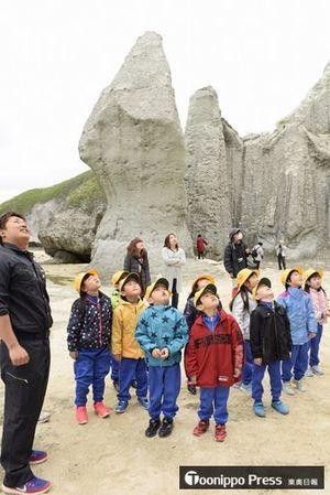 福田さん(左)の案内で仏ケ浦を散策し、奇岩を見上げる佐井小1年生