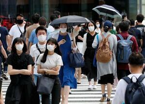 東京・銀座で日傘を差して歩くマスク姿の人ら=1日午後