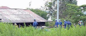全焼した空き家(写真奥)や周辺を実況見分する警察官ら=22日午前、むつ市川守町