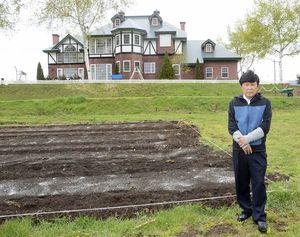 「アグリインホリデー」の英国風宿泊施設と渡邉さん。手前が5日にオープンする市民農園