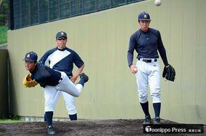 兜森監督(後ろ)が見守る中、投球練習をする主戦三上(左)と斉藤勇=17日午後、大阪府高槻市