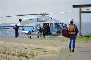 救助した男性をヘリから降ろす救急隊員ら=21日午後4時35分ごろ、平内町東田沢横峰