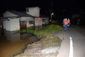 馬淵川につながる水路からあふれた水に漬かった空き屋=12日午後7時42分、八戸市櫛引
