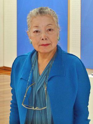 自作の前に立つ佐々木さん。「青は深い精神を表すのにいちばん適した色」=世田谷美術館