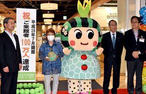 つがる市立図書館の来館100万人目になった長内さん(左から2人目)