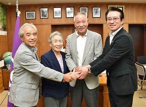 吉田町長(右)と握手を交わす駒木さん夫妻(中)と八木橋さん(左)