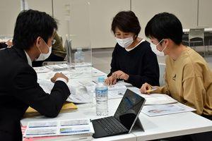 大学担当者(左)から説明を受ける参加者