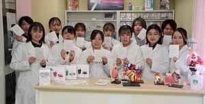 県登録販売者試験の合格通知書を手に笑顔を見せる学生12人