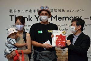 来館1万人目となった山家さん一家に記念品を手渡す三上館長(右)=10日午前