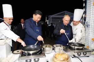 ロシア風クレープ「ブリヌイ」を焼くプーチン大統領(右から2人目)と中国の習近平国家主席=11日、ロシア極東ウラジオストク(タス=共同)