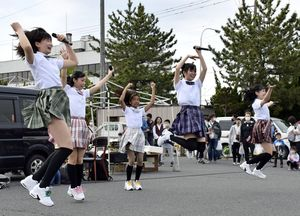 マイクを手に持ち踊るpacchiのメンバー。ヘッドマイクになれば、よりキレのあるダンスを披露できるという=5月、八戸市の館鼻岸壁朝市