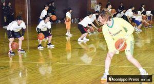 中村選手(右)からドリブルの仕方について指導を受ける生徒たち