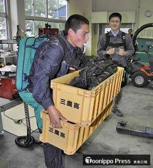 アシストスーツを装着し、ナガイモ入りコンテナ(重さ約25キロ)を軽々と持ち上げる生徒
