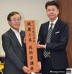 共同研究講座のプレートを掲げる工藤社長(右)と佐藤学長