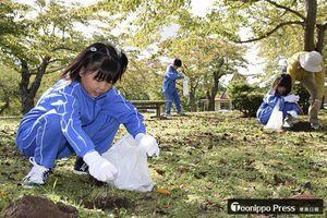 きれいな桜が咲くよう祈りながら、土に肥料を入れた児童たち=むつ市の早掛沼公園
