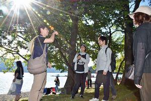 山下さん(左)のガイドで湖畔を巡る「夏さんぽ」に参加した観光客
