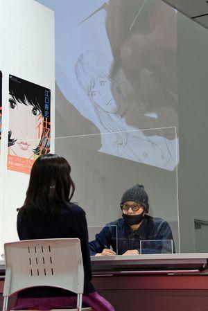 江口さんが描く様子はスライドで上映=10日、青森市の東奥日報新町ビル