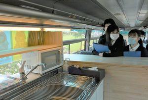 改造した大型バスの車内を見学する八工大二高生ら
