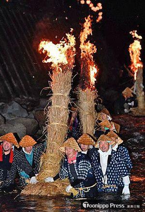 急流に足を取られながら、燃えるカヤ舟を操り、中野川を下る男衆=16日夜、黒石市大川原