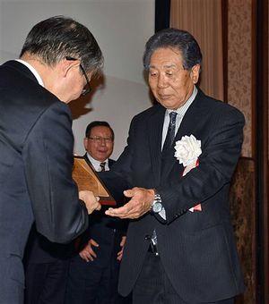山口会長(左)から記念の盾を受け取る大柳さん