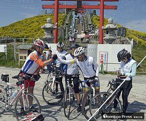 約800キロを自転車で走破し、ゴールの蕪島で健闘をたたえ合う参加者=5日午後