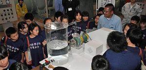 模型のポンプを動かし、水をくみ上げる仕組みの説明を熱心に聞く児童たち