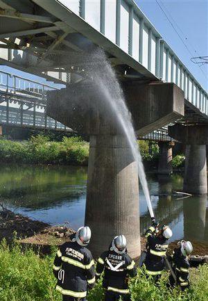 煙が上がる線路の枕木に放水する消防隊員=2日午後2時55分、南部町沖田面