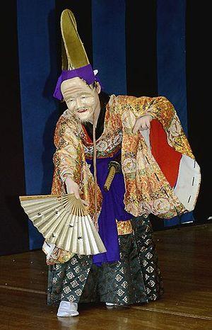白い面を着け「翁舞」を踊る川端さん