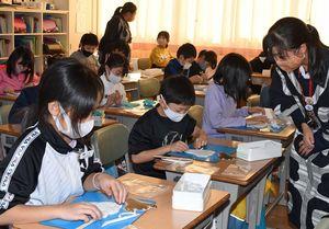 木造高生の説明を受けながら、粘土で形作った縄文土器に模様を付ける向陽小3年生児童たち