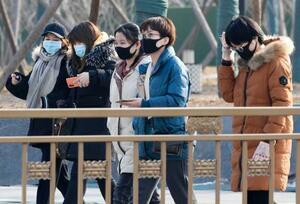 マスクを着用して北京市内を歩く人たち。中国では新型コロナウイルスの感染の拡大が続いている=22日(共同)