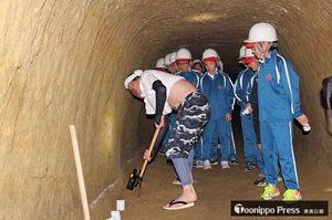 公開1周年となる「幻の穴堰」。十和田歴史文化研究会会員が江戸期の掘削作業の様子を再現し、児童たちが興味深げに見入った=9月22日(同研究会提供)