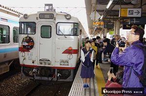 この日だけのヘッドマーク(車体前面左側)を装着したキハ40系車両の前で記念撮影するファンら=16日午前9時すぎ、JR八戸駅