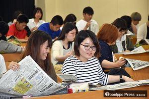 「新聞の読み方講座」で、東奥日報朝刊を読む学生たち=八戸工業大学