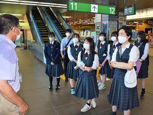 櫛引教授(左)の説明を聞きながら、新青森駅内を見学する長万部高校の生徒ら