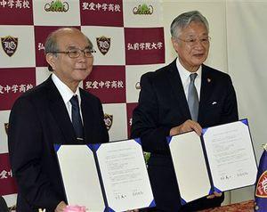基本協定書を取り交わし笑顔を見せる弘学大の吉岡学長(右)と青学大の三木学長