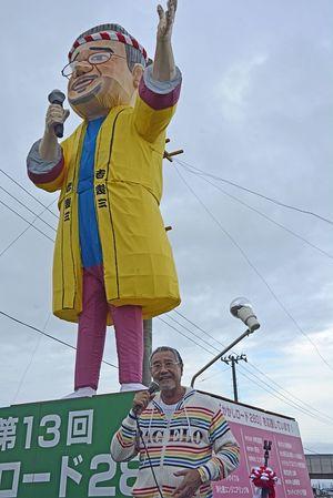 吉幾三さんをイメージした巨大かかしの前であいさつする吉さん