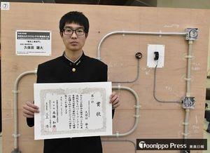 自身の作品の前で1位の賞状を手にする弘前工2年の久保田さん