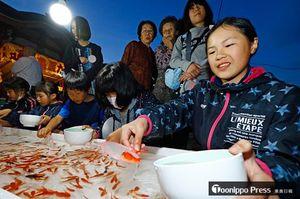 歓声を上げて金魚すくいを楽しむ子どもたちでにぎわった宵宮=21日午後7時10分ごろ、大鰐町の大円寺