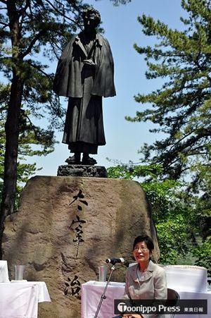 太宰像の前であいさつする長女の津島園子さん
